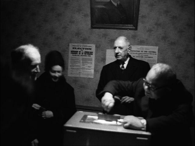 Le général de Gaulle (C) et son épouse (2eG) s'apprêtent à déposer leur bulletin de vote dans l'urne à la mairie de Colombey-les-Deux-Eglises, le 19 décembre 1965