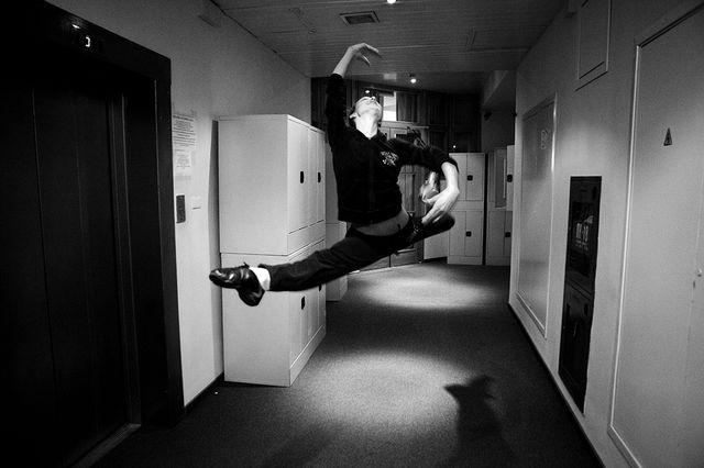 Une danseuse profite de quelques instants avant de rentrer en salle de répétition pour montrer  sa technique de saut à un professeur qu'elle croise dans un couloir/ Ballet du Bolchoï 04/11