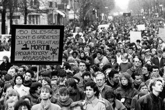 Plusieurs milliers de personnes manifestent silencieusement, à Paris le 6 décembre 1986, de la place de la Sorbonne à l'hôpital Cochin où repose le corps de Malik Oussekine;