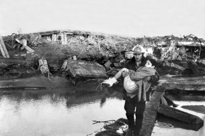 Un pompier emporte dans ses bras un jeune garçon qu'il vient de sauver de sa maison en ruine le 3 décembre 1959, après la catastrophe de Malpasset.