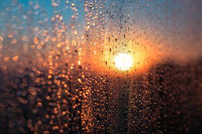 Lever de soleil vu derrière une vitre et de la condensation