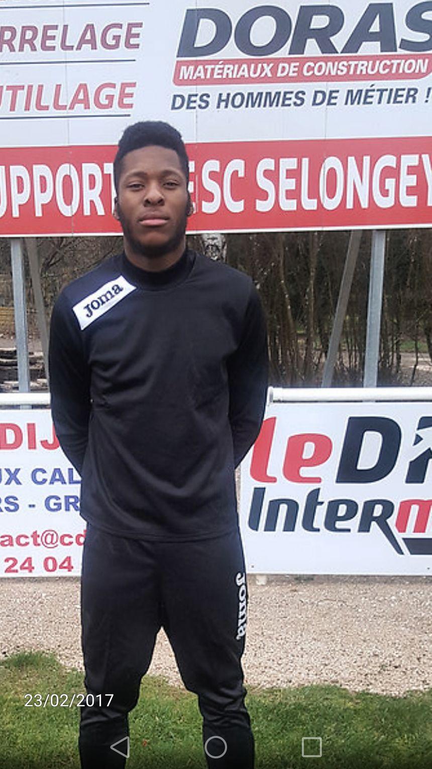 Théo pose devant un panneau publicitaire du Stade des Courvelles de Selongey