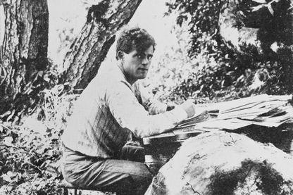 Jack London (1876 - 1916) en train d'écrire dehors