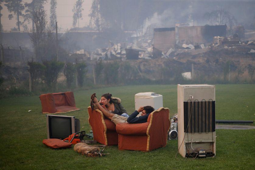 Un couple se reposant dans un terrain de foot à Santa Olga après l'incendie de la forêt (Chili)
