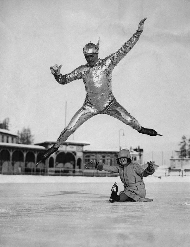 Le champion du monde de patinage Phil Taylor saute au-dessus de sa fille Megan sur la patinoire de l'hôtel Kulm à St. Moritz, en Suisse vers 1930