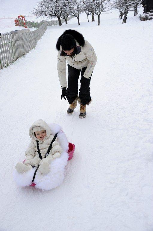 A Morzine (Haute Savoie) une mère pousse sa fille dans une luge