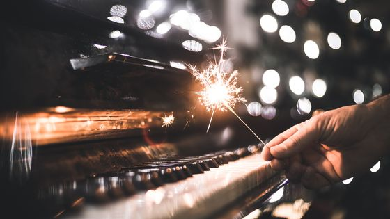 hand holding a sparkler over a piano