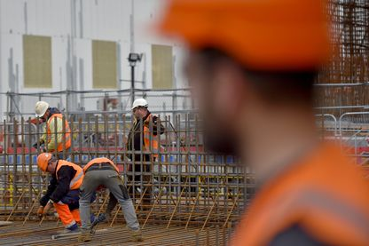 travailleurs construisent une structure flottante en béton;