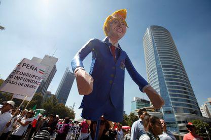 Une femme porte une effigie du président des États-Unis Donald Trump lors d'une marche pour protester contre le mur frontière proposé par Trump et de demander l'unité, à Mexico, le 12 février 2017