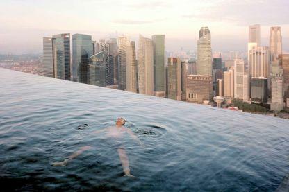Un homme flotte au 57 ème étage dans la piscine du Marina Bay Hôtel, avec vue sur les grattes-ciel du quartier d'affaire de Singapour