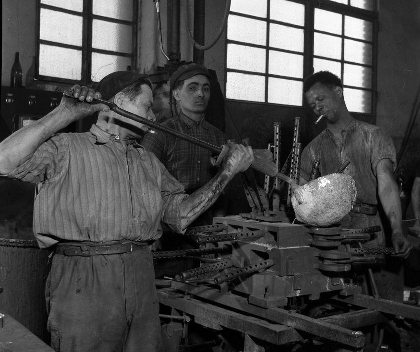 Plan Marshall ou Programme de retablissement europeen (European Recovery Program ou ERP) (1948-1952) : dans une usine francaise, deux ouvriers nord africains et un ouvrier polonais moulent une piece de moteur de motocyclette.