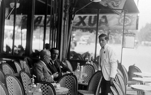 Maurice Ravel assis en terrasse d'un café parisien avec un ami, en 1930.