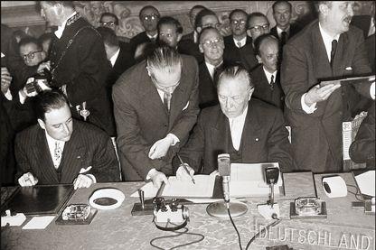 Sur la photo, le Chancelier Adenauer signe le traité de Rome en 1957. La RFA, l'Italie, la Belgique, les Pays-Bas, le Luxembourg et la France signent le traité pour coordonner les politiques économiques des six pays signataires.