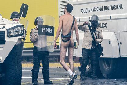Un manifestant vénézualien nu se confronte avec la police anti-émeutes lors d'une manifestation contre le président Nicolas Maduro, à Caracas le 20 avril 2017.