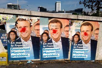 Tags sur des affiches d'Emmanuel Macron à Paris