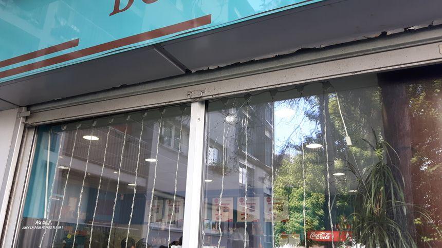 L'impact de balle visible sur la façade de la boulangerie face à l'entrée de l'hôpital