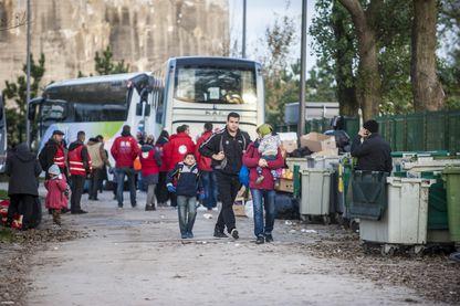 """Une famille de réfugiés s'apprête à monter dans un bus après avoir quitté la réception du centre """"Jules Ferry"""", à Calais, le 3 novembre 2016."""