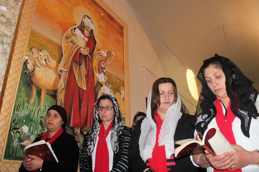 A Mossoul, troisième ville d'Irak, des femmes arabes prient durant la messe de Pâques, devant un portrait du Christ défiguré par les troupes armées de l'Etat Islamique avant leur départ
