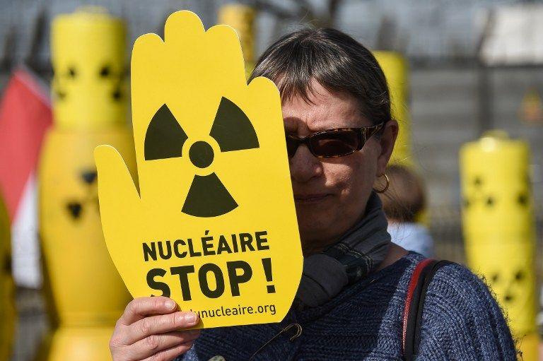 Une femme brandit une pancarte durant une manifestation pour la fermeture de la centrale de Fessenheim en mars 2017