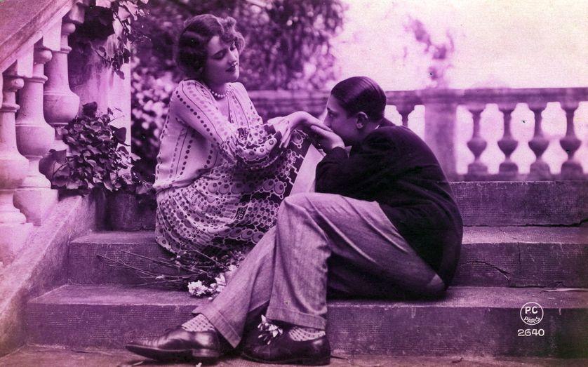 Un couple assis sur un escalier, l'homme embrasse les mains de sa compagne en la regardant, 1925