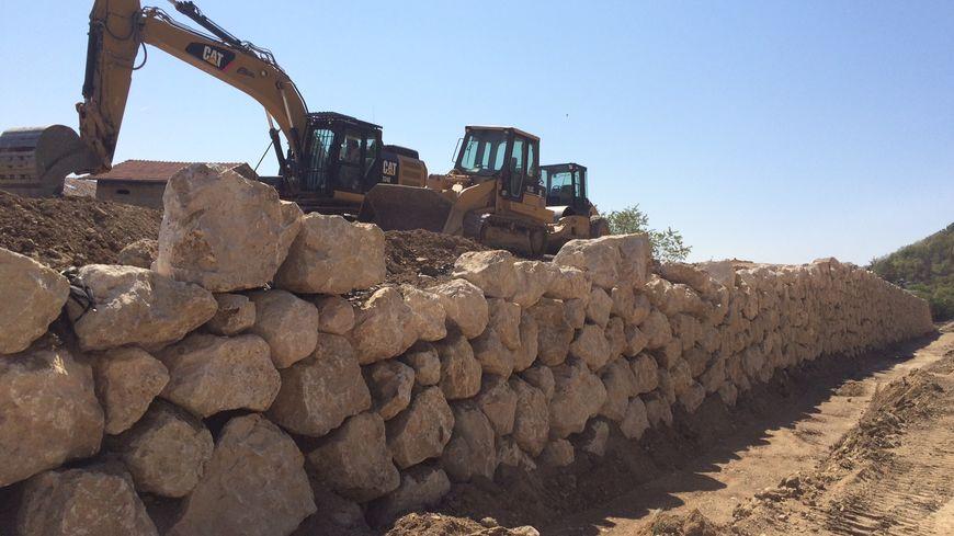 Un merlon, une grande butte de terre de 220 mètres de long et 6,5 mètres de haut, est construit au pied de la falaise de Crussol pour retenir les blocs de pierre en cas d'éboulement.