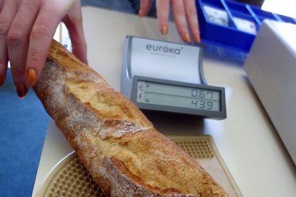 Une personne se familiarise à l'euro avec un convertisseur en payant une baguette du pain 0.67 Euro soit 4.40 francs, le 20 juin 2001 à Epinal.