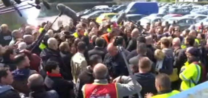 Macron échange avec les salariés au milieu des journalistes.