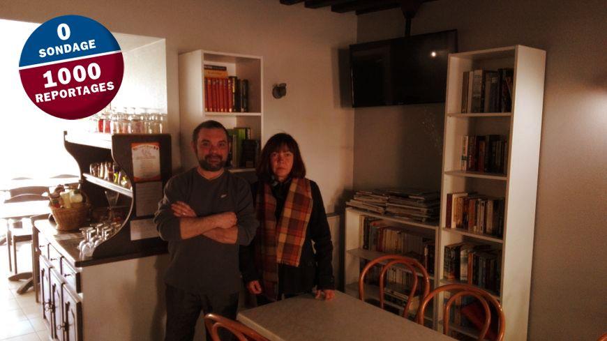 Sébastien le commerçant et Nathalie une cliente à côté des livres
