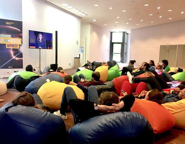 Les curieux qui n'ont pas eu de places dans l'auditorium se retrouvent par dizaines sur des poufs devant un écran qui retransmet les conférences.