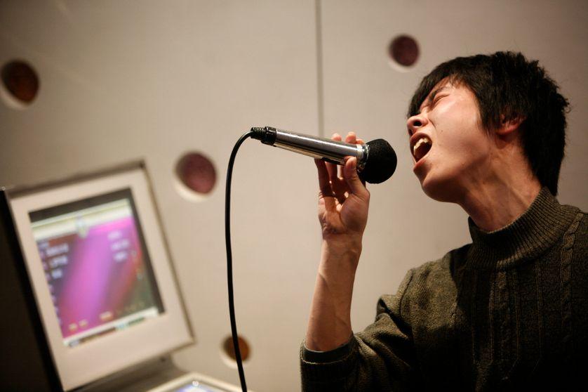 Un jeune homme chante dans un karaoke club à Shangaï
