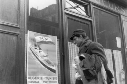 Un homme d'origine nord-africaine regarde les voyages publicitaires d'affiches en Algérie et en Tunisie, accrochées à la fenêtre d'un café nord-africain dans le quartier La Chapelle de Paris, en avril 1950.