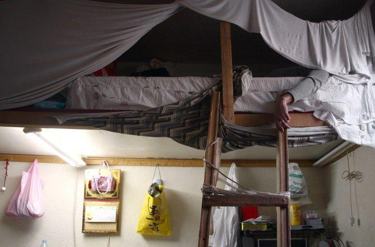 Un sans-papiers chinois est allongé dans son lit, le 22 octobre 2007 dans son appartement à Paris