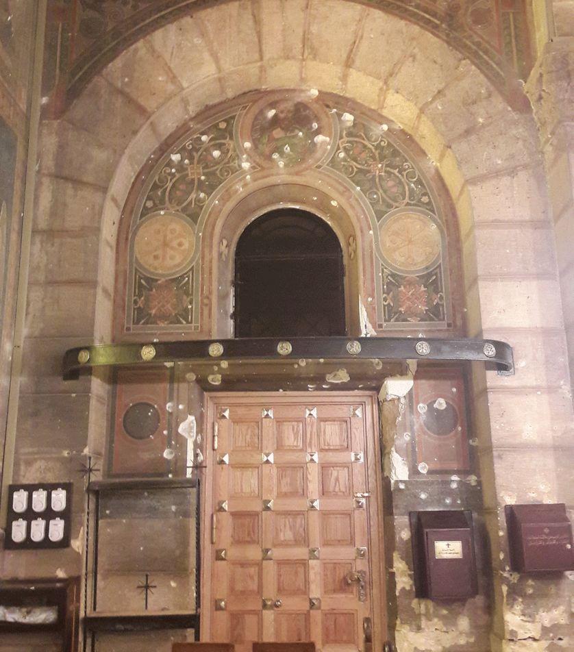 Porte d'entrée de l'Eglise de La Botroseya criblée de balles lors de l'attentat du 11 décembre 2016 revendiqué par le groupe Etat Islamique