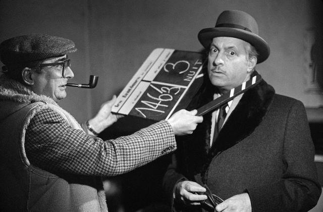 """Le réalisateur français Claude Chabrol (G) joue avec le clap devant le visage de Michel Serrault lors du tournage du film """"Les Fantômes du chapelier"""" d'après le roman de Georges Simenon, qui a débuté à Concarneau, le 20 janvier 1982."""