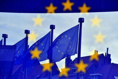 Drapeaux européens se reflétant à l'entrée de l'immeuble Berlaymont à Bruxelles
