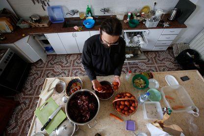 Sergey, prêtre chrétien, prépare les oeufs de Pâques traditionnels pour la prière du soir en les faisant bouillir dans de l'eau contenant des peaux d'oignons pour les colorer à l'église rocheuse orthodoxe russe d'Mamre en Cisjordanie en avril 2017.