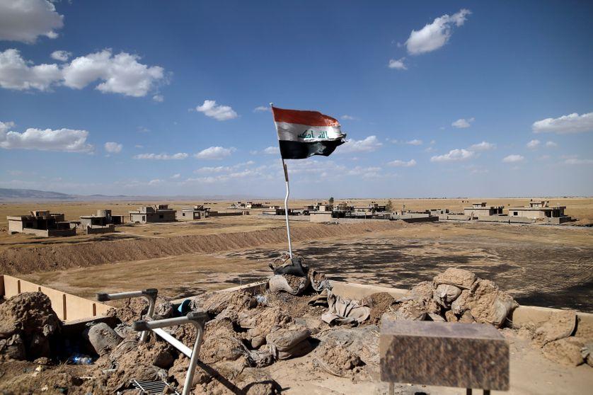 Drapeau irakien flottant sur le toit d'une école récemment libérée du groupe Etat islamique, dans le village de Kojo, Irak, 1er  juin 2017