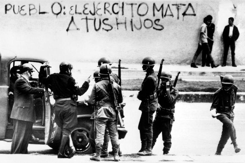 """Photo prise le 4 août 1968 à Mexico de militaires à l'intérieur de l'université de la ville, occupée par les étudiants depuis juillet. Sur le mur est écrit: """"Pueblo: el ejercito mata tus hijos / Peuple, l'armée tue tes enfants"""""""