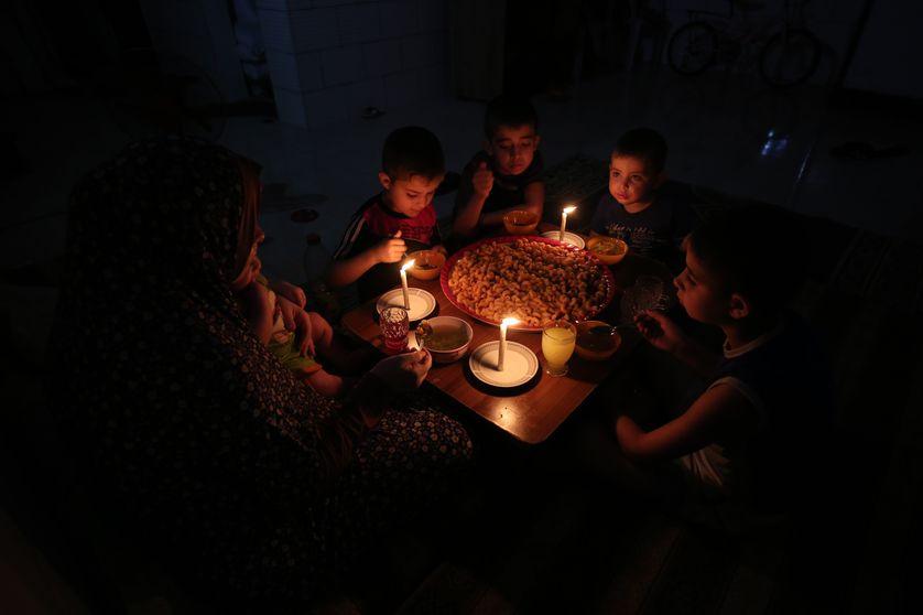 Une famille palestinienne s'éclaire à la bougie pendant les heures de coupures de l'approvisionnement en électricité
