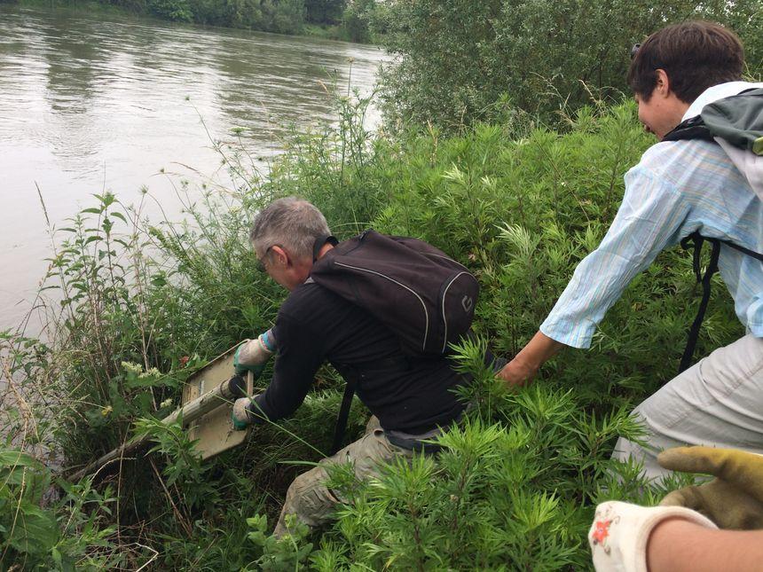 """Deux """"ramasseurs"""" bénévoles tentent tant bien que mal d'extraire de la vase un panneau de signalisation perdu dans les berges du fleuve."""