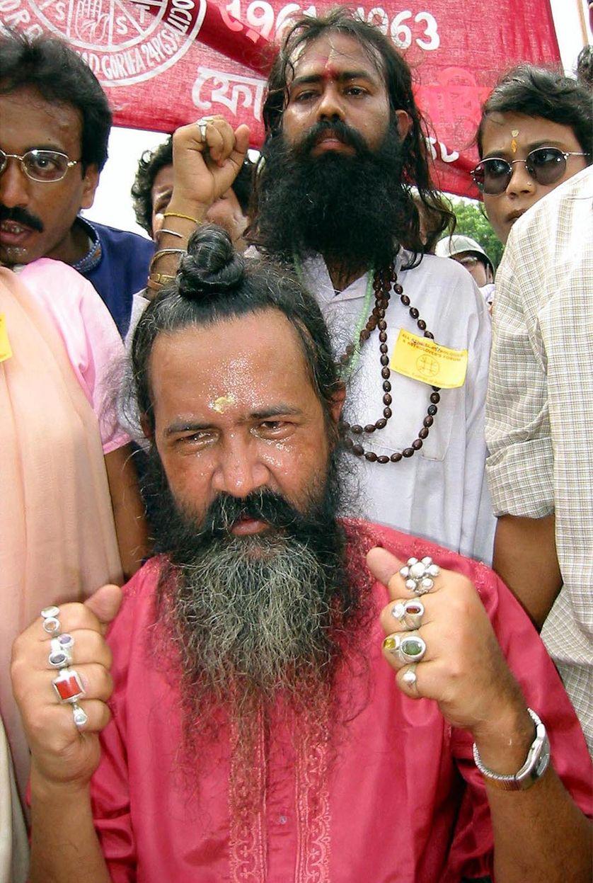 Un astrologue portant des bagues, qui selon lui lui donne le pouvoir de changer le destin, à Calcutta, Inde, 27 juillet 2001