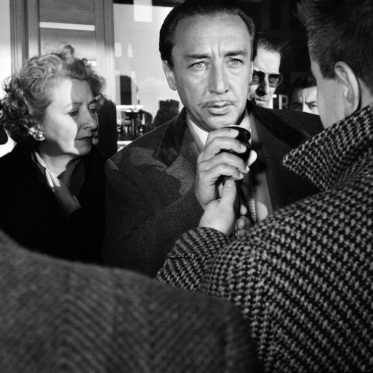 """L'écrivain français Romain Gary, récompensé par le """"Prix Goncourt"""" pour son livre """"Les racines du ciel"""" répondant à un journaliste au côté de sa femme lors de son arrivée à l'aéroport d'Orly le 13 décembre 1956."""