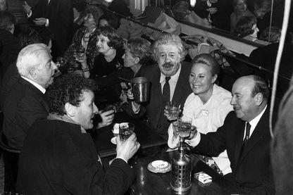 Jacques Prévert (G) et au réalisateur Marcel Carné (D), en présence des acteurs Jean-Louis Barrault (2e G), Michel Simon (C) et Michèle Morgan - Café des Deux Magots, Paris - 24/02/1967