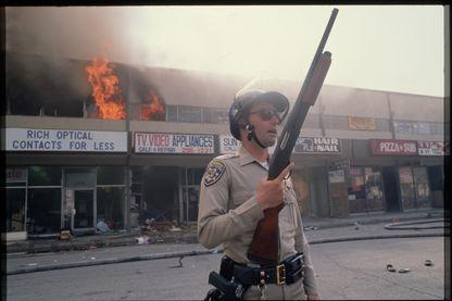 Un agent de la patrouille routière de la Californie garde la garde d'une rue protégeant les magasins, endommagé par les émeutes, contre les pillards le 1er mai 1992