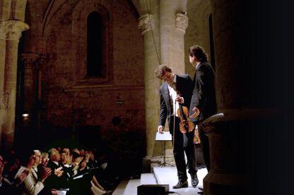 Le chef d'orchestre et violoniste, Jean-Christophe Spinosi (C), accompagné du contre-ténor David DQ Lee, salue le public le 18 septembre 2009 à l'abbaye d'Ambronay après un concert de l'ensemble