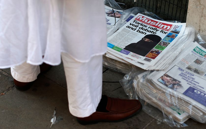 Un homme regarde un journal annonçant un débat des conservateurs autour du voile intégral à la sortie du mosquée à Londres.