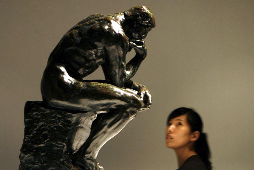 """Le """"Penseur"""" d'Auguste Rodin contemplé par une visiteuse"""