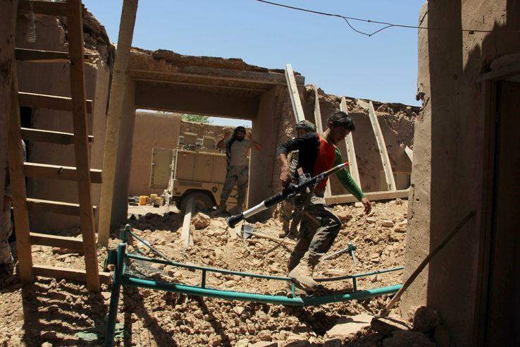 Des membres de la police des frontières afghane parcourent un avant-poste sévèrement endommagé par une frappe aérienne dans le quartier de Nad Ali dans la province d'Helmand, le 10 juin 2017.
