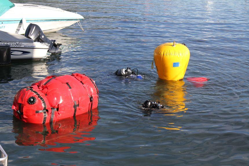 La barque est ramenée vers la surface par de gros ballons d'air, sous la surveillance de deux plongeurs.