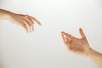 Des mains s'entendent l'une vers l'autre